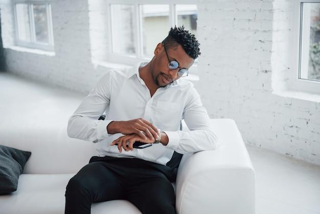 Bewondert het nieuwe polshorloge. stijlvolle afro-amerikaanse man in klassieke kleding en bril zit op het bed
