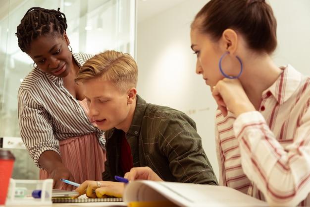 Bewuste leerling. geconcentreerde jonge mannelijke persoon die aan tafel zit terwijl hij zijn taalvaardigheid demonstreert