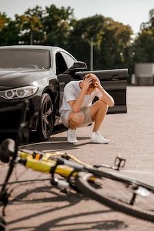 Bewustwording van het probleem. wanhopige gemberman in t-shirt en korte broek gehurkt bij zwarte auto na ongeval en fiets die op de weg ligt