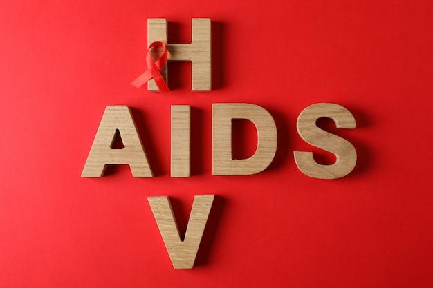 Bewustzijnslint en woorden aids en hiv op rode muur, ruimte voor tekst