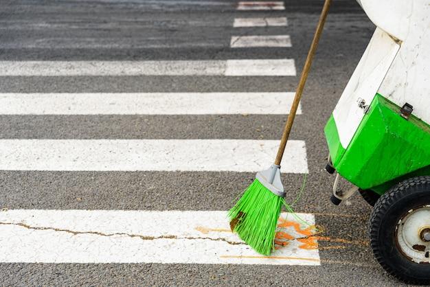 Bezem van een openbare werknemer van de straatveger houdt de stad schoon.