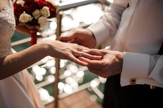 Bezem zetten een mooie gouden trouwring aan de vinger van een tedere bruid op de achtergrond van de stralende zee