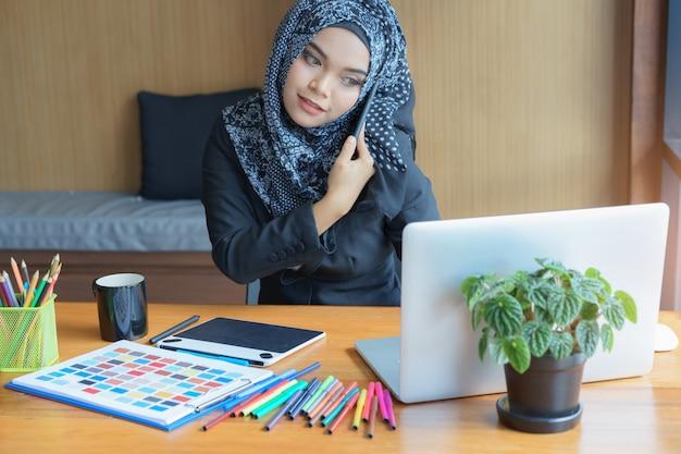 Bezige aziatische moslim bedrijfsvrouw die op mobiele telefoon in modern bureau spreekt.