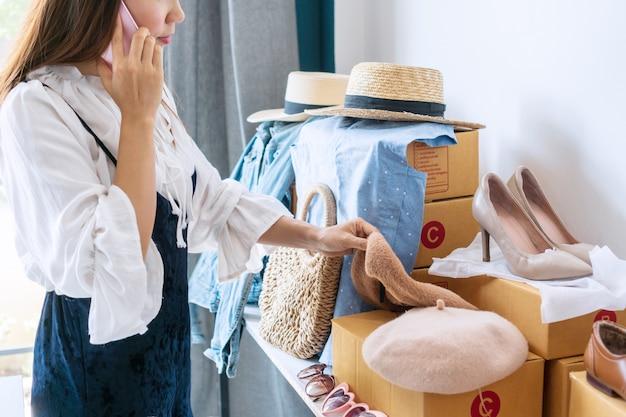 Bezige jonge aziatische bedrijfsondernemer die op de telefoon met klant spreekt terwijl het controleren van voorraadsaldo. online verkoop, e-commerce, zaken en technologie, nieuw normaal concept