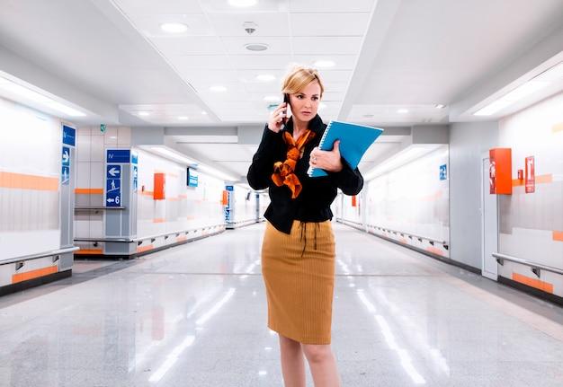 Bezige vrouw ceo manager in de hal van het bedrijfsleven bouwen met behulp van telefoon en het controleren van documentbestand. zakenvrouw in moderne hallaway gaat werken