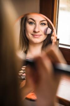 Bezinning van een glimlachende vrouw die blusher op haar gezicht toepast
