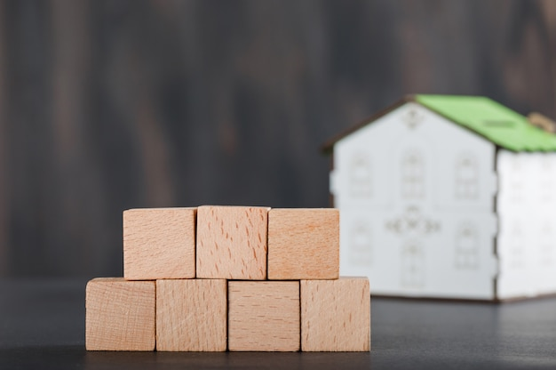 Bezitsconcept met houten kubussen, huismodel en grijs.