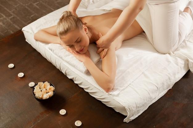 Bezoek aan spa-centrum. kalme jonge vrouw met blond haar die door een massagesessie gaat terwijl ze op een matras in een kast ligt
