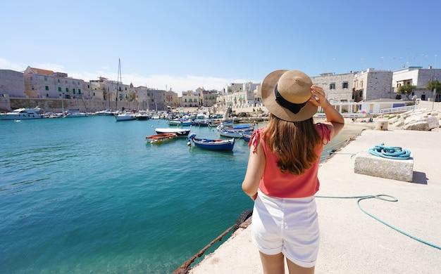 Bezoek italië. achteraanzicht van jonge vrouwelijke toerist die hoed vasthoudt en op zoek is naar de haven van giovinazzo in apulië, italië.