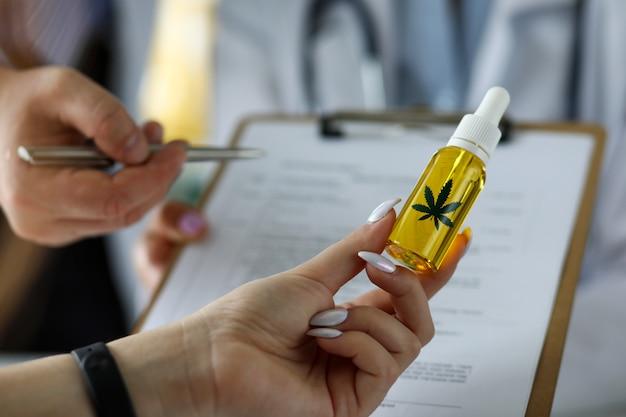 Bezoeker hand met potje cannabis concentraat olie