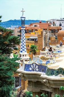 Bezoekers van parc guell op een uitkijkpunt met een ongewoon stadsbeeld in bouwstijl van barcelona