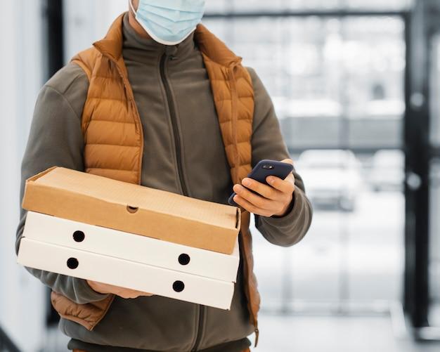 Bezorg de man met het pakket van de maskerholding van dichtbij