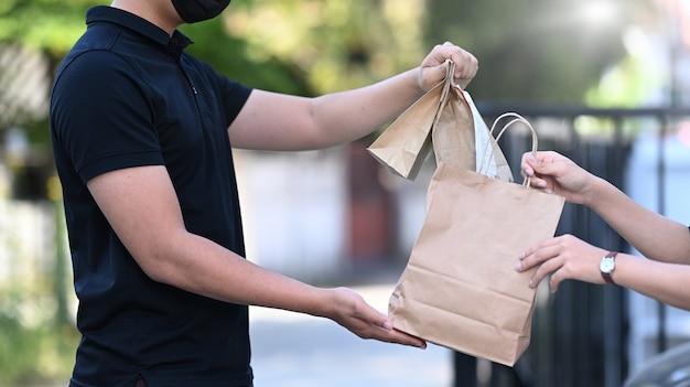 Bezorg een man die een papieren zak met voedsel hanteert en geef deze aan de vrouwelijke klant bij de deuropening.