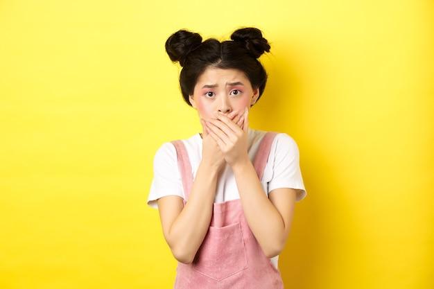 Bezorgd aziatisch tienermeisje dat mond bedekt met handen, bezorgd en angstig kijkt, bang op geel staat met glamoureuze make-up en zomerkleding.
