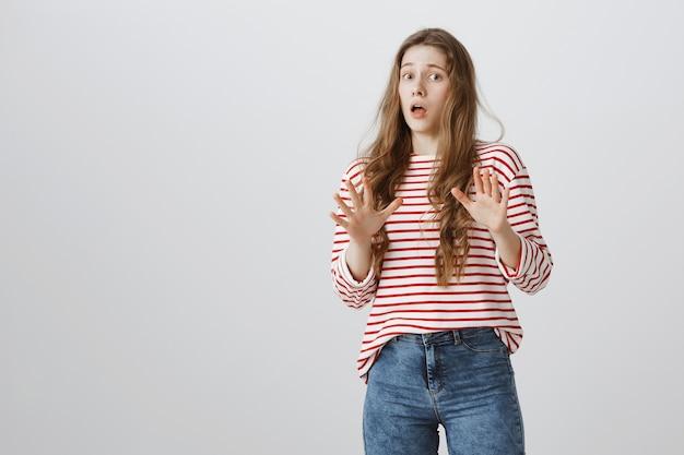 Bezorgd bang meisje dat handen opheft en geschrokken een stap achteruit doet