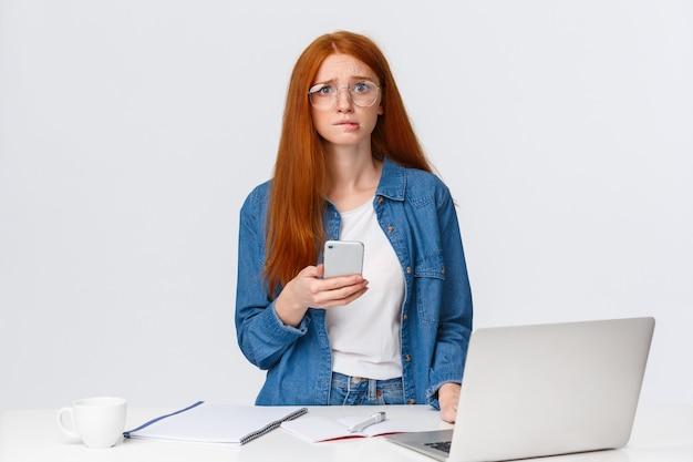 Bezorgd, bezorgd schattig roodharig meisje nerveus op zoek naar camera en bijt lip, heb een probleem, kan de deadline niet halen, houdt smartphone vast, staat in de buurt van laptop en een bureau, wit