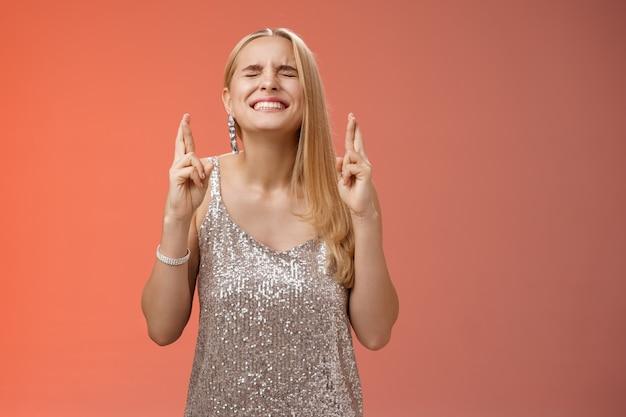 Bezorgd blonde vrouw moeite god hoor gebeden intens sluiten ogen balde tanden hoofd omhoog bidden smekend kruis vingers veel geluk wil winnen droom die uitkomt wensen, rode achtergrond.