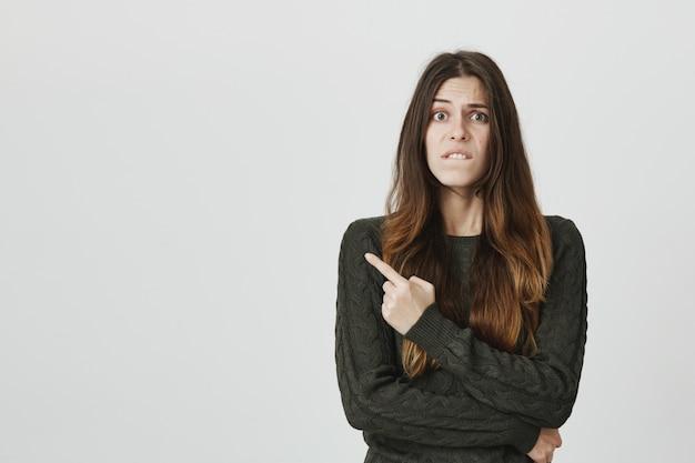 Bezorgd en besluiteloos jonge vrouw lip bijten, advies vragen en wijzende vinger naar links