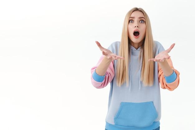 Bezorgd en bezorgd blond europees meisje hijgend, mond open en handen opstekend om iets op te vangen dat uit de lucht valt