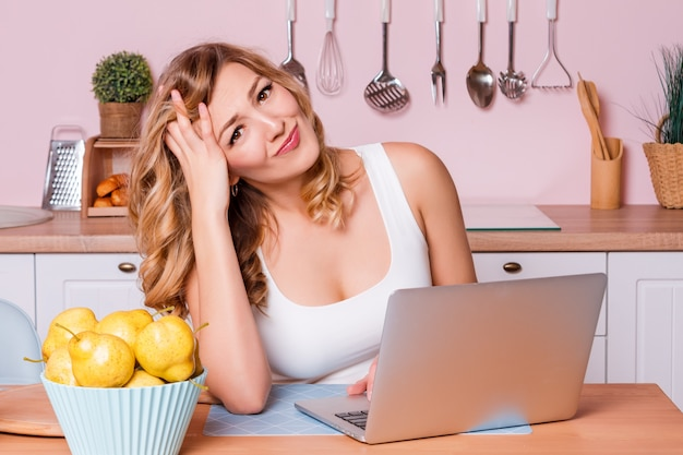 Bezorgd en droevig studentenwijfje die informatie zoeken in laptop online zitting in de keuken.