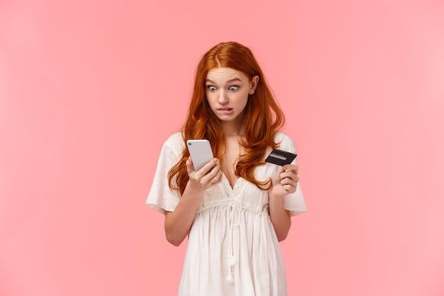 Bezorgd en onhandig schattig roodharig meisje maakte een fout, verspilde per ongeluk al het geld van de vriend tijdens het winkelen, zag er schuldig uit met oeps gezicht starend smartphone-display, met creditcard