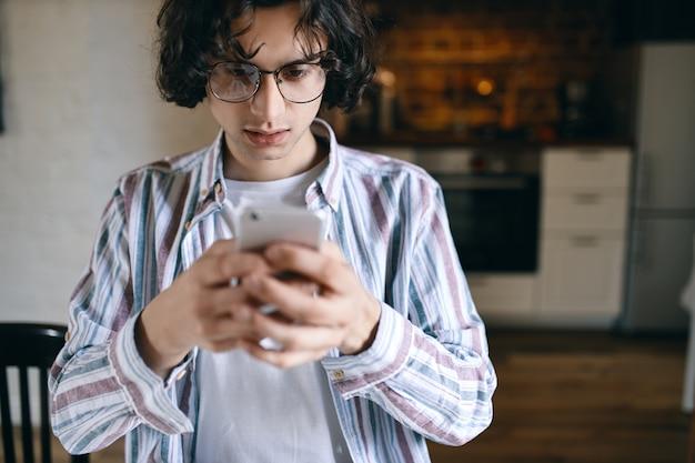 Bezorgd ernstige jonge man met slimme telefoon, scherm kijken met gefrustreerde gezichtsuitdrukking, tekstbericht lezen, slecht nieuws ontvangen.