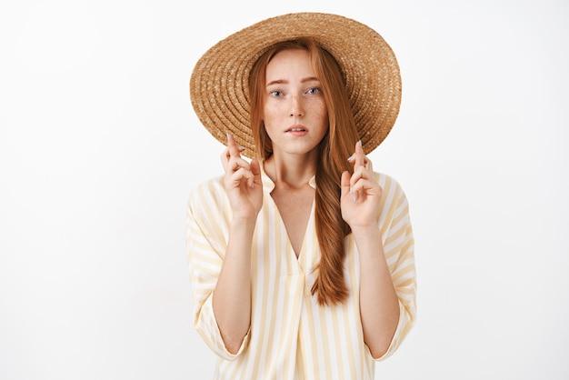 Bezorgd geconcentreerd knap gembermeisje met sproeten in schattige zomer strooien hoed en gestreepte blouse vingers kruisen voor geluk bezorgd kijken en bezorgd bidden, wens doen