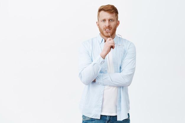 Bezorgd gefocuste aantrekkelijke blanke man met rood haar en borstelharen bijt op de rand van een bril terwijl hij zenuwachtig staart, nadenkt over problemen, probeert het in gedachten op te lossen, uitweg zoekt