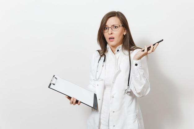 Bezorgd geschokt arts vrouw met stethoscoop, geïsoleerd op een witte achtergrond. vrouwelijke arts in medische toga praat op mobiele telefoon, houd gezondheidskaart op notitieblokmap. gezondheidszorg personeel concept.