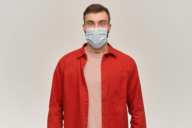 Bezorgd geschokte jonge bebaarde man in rood shirt en virusbeschermend masker op gezicht tegen coronavirus staan en kijken naar voorkant over witte muur