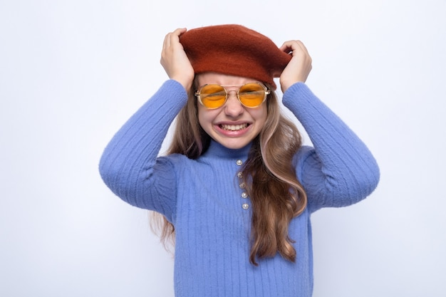 Bezorgd greep het hoofd mooi klein meisje met een bril met hoed geïsoleerd op een witte muur