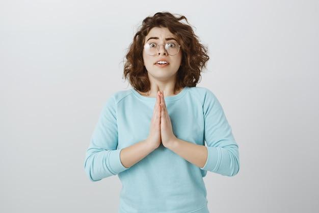 Bezorgd hoopvol meisje dat om hulp smeekt, smeekt, om gunst vraagt