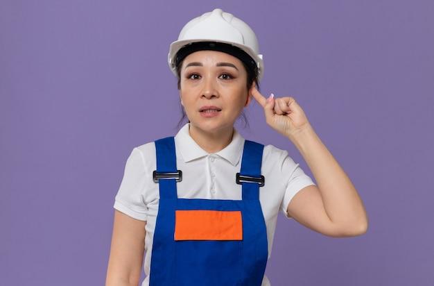 Bezorgd jong aziatisch bouwersmeisje dat met witte veiligheidshelm haar oor met vinger sluit