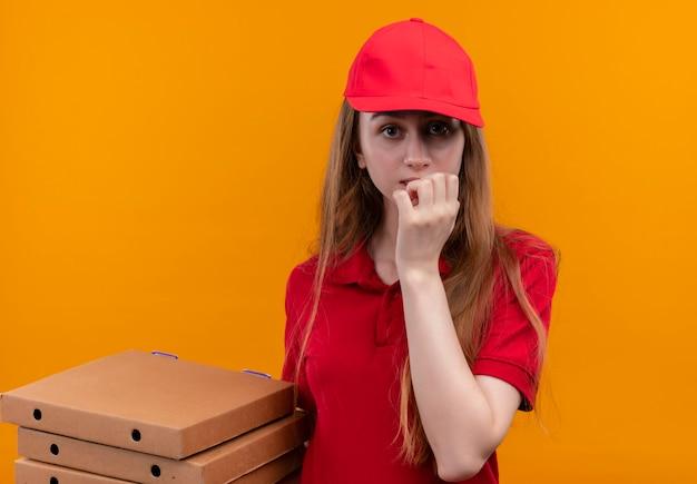 Bezorgd jong bezorgmeisje in rode uniforme bedrijfspakketten met hand op lippen op geïsoleerde oranje ruimte