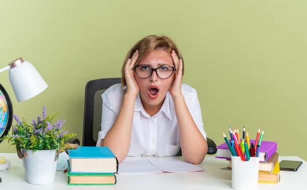 Bezorgd jong blond studentenmeisje met een bril die aan het bureau zit met schoolhulpmiddelen die de handen op het hoofd houden en naar de camera kijken die op de olijfgroene muur is geïsoleerd