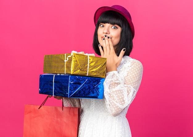 Bezorgd jong feestmeisje met feestmuts met papieren zak en geschenkpakketten die de hand op de mond houden geïsoleerd op roze muur met kopieerruimte