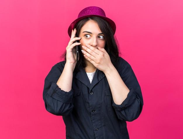 Bezorgd jong kaukasisch feestmeisje met een feesthoed die aan de telefoon praat en naar de zijkant kijkt en de hand op de mond houdt, geïsoleerd op een roze muur