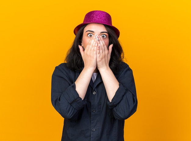 Bezorgd jong kaukasisch feestmeisje met een feesthoed die de handen op de mond houdt en naar de voorkant kijkt geïsoleerd op een oranje muur met kopieerruimte
