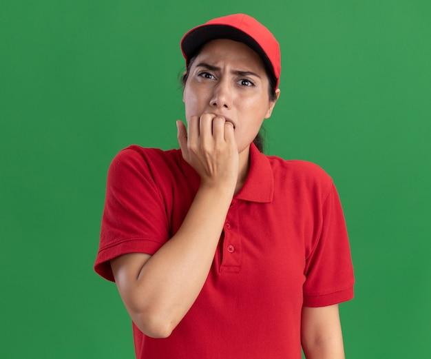 Bezorgd jong leveringsmeisje die eenvormig en glb dragen bijt spijkers die op groene muur worden geïsoleerd