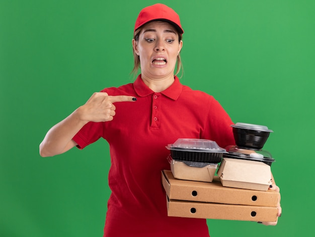 Bezorgd jong mooi bezorgmeisje in uniform houdt en wijst naar papieren voedselpakketten en containers op pizzadozen op groen