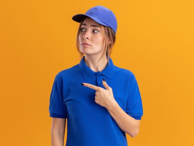 Bezorgd jong mooi bezorgmeisje in uniform uiterlijk en wijst naar de zijkant op oranje Gratis Foto