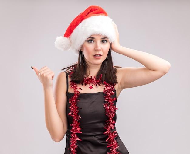 Bezorgd jong mooi kaukasisch meisje met een kerstmuts en een klatergoudslinger om de nek kijkend naar de camera die de hand op het hoofd houdt en naar de zijkant wijst geïsoleerd op een witte achtergrond