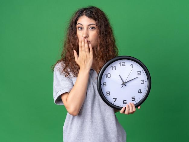 Bezorgd jong, mooi kaukasisch meisje met een klok die de hand op de mond houdt, geïsoleerd op een groene muur met kopieerruimte