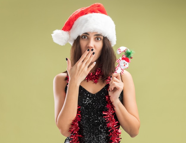 Bezorgd jong mooi meisje met kerstmuts met guirlande op nek met kerstspeelgoed bedekte mond met hand geïsoleerd op olijfgroene achtergrond