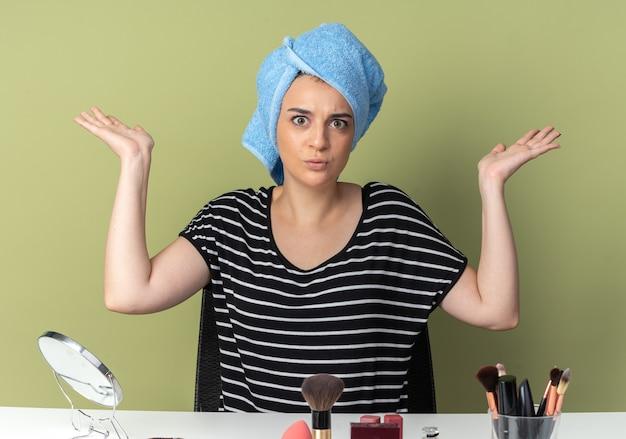 Bezorgd jong mooi meisje zit aan tafel met make-uptools gewikkeld haar in handdoek spreidende handen geïsoleerd op olijfgroene muur