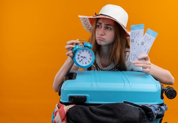 Bezorgd jong reizigersmeisje die de vliegtuigkaartjes en wekker van de hoed houden met koffer op geïsoleerde oranje ruimte met exemplaarruimte