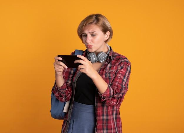 Bezorgd jong slavisch studentenmeisje met hoofdtelefoons die rugzak dragen die houden en naar telefoon kijken