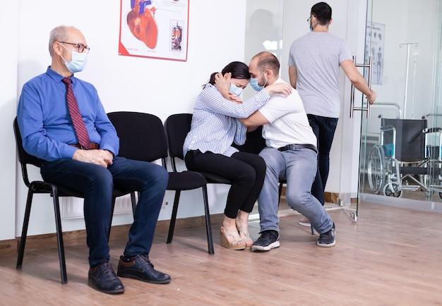 Bezorgd jong stel dat gezichtsmasker draagt tegen infectie met coronavirus tijdens het wachten op nieuws van de dokter