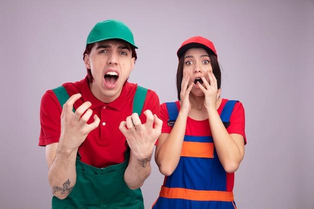 Bezorgd jong stel in bouwvakkeruniform en pet-man met lege handen meisje houdt handen in de buurt van gezicht, beide kijkend naar camera geïsoleerd op een witte muur