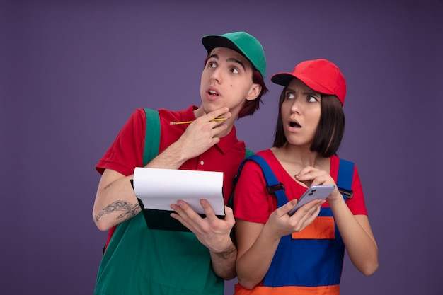 Bezorgd jong stel in bouwvakkeruniform en pet-man met potlood en klembord die hand op kin houdt meisje met mobiele telefoon die beide omhoog kijkt Gratis Foto